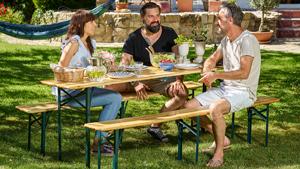 Personen sitzen auf einer Bierzeltgarnitur im Garten
