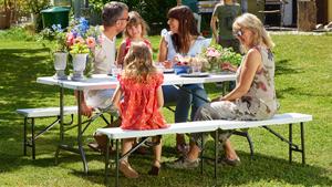 Personen sitzen an einer Bierzeltgarnitur im Garten